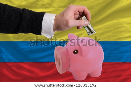 Man putting dollar into piggy rich bank national flag of columbia in foreign currency because of inflation