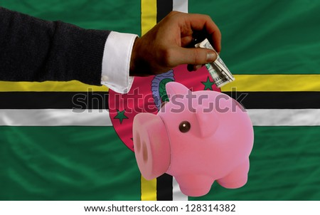 Man putting dollar into piggy rich bank national flag of dominica in foreign currency because of inflation - stock photo