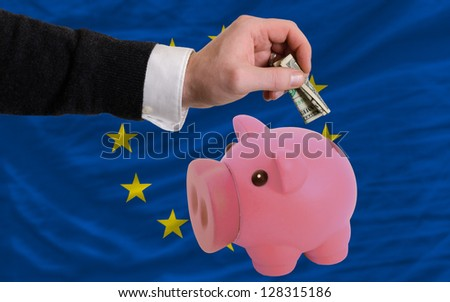 Man putting dollar into piggy rich bank national flag of europe in foreign currency because of inflation - stock photo