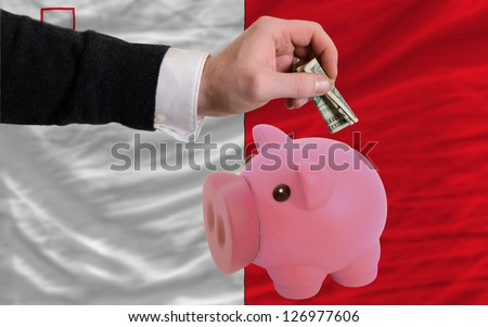 Man putting dollar into piggy rich bank national flag of malta in foreign currency because of inflation - stock photo