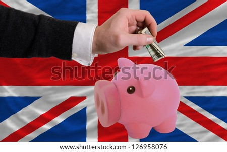 Man putting dollar into piggy rich bank national flag of uk in foreign currency because of inflation - stock photo