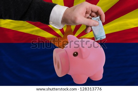 Man putting euro into piggy rich bank and flag of us state of arizona in foreign currency because of insecurity and inflation