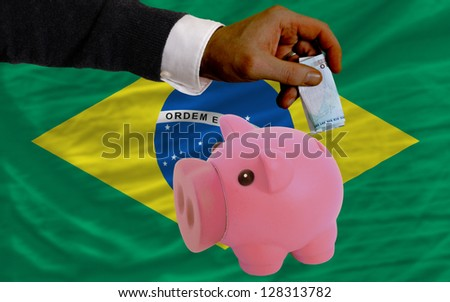 Man putting euro into piggy rich bank and national flag of brazil in foreign currency because of insecurity and inflation - stock photo