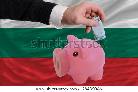 Man putting euro into piggy rich bank and national flag of bulgaria in foreign currency because of insecurity and inflation - stock photo