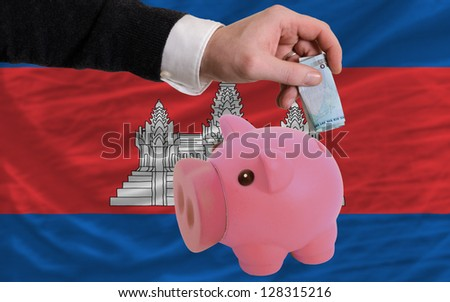 Man putting euro into piggy rich bank and national flag of cambodia in foreign currency because of insecurity and inflation - stock photo
