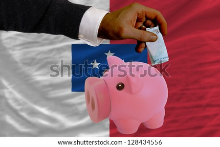 Man putting euro into piggy rich bank and national flag of  franceville in foreign currency because of insecurity and inflation - stock photo