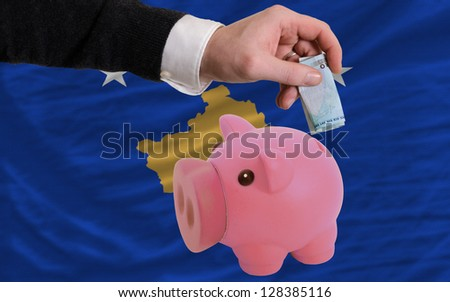 Man putting euro into piggy rich bank and national flag of  kosovo in foreign currency because of insecurity and inflation - stock photo