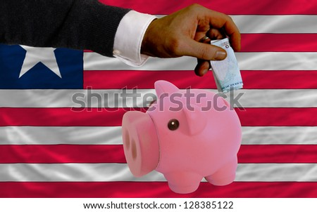 Man putting euro into piggy rich bank and national flag of liberia in foreign currency because of insecurity and inflation - stock photo