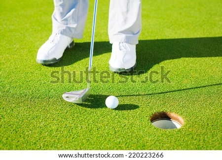 Man Putting Golf Ball into the Hole, Close up detail Shot - stock photo