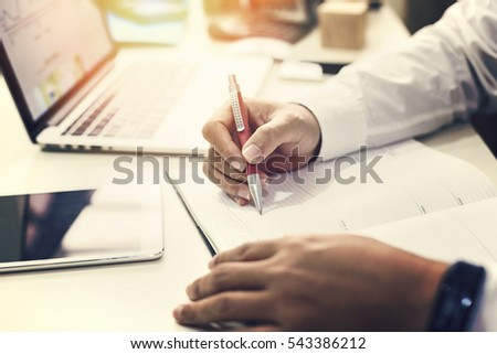 Man putting her ideas and writing business plan at workplace, man holding pens and papers, making notes in documents on the table in office, vintage color, morning light , selective focus.