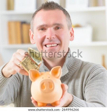Man putting money in piggybank, concept of saving - stock photo