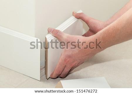 Man putting new skirting board in house - stock photo