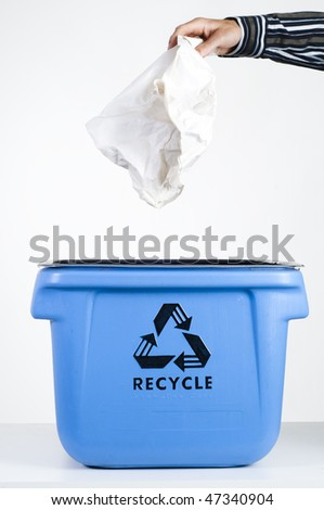 Man putting paper into blue recycling box - stock photo