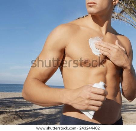 Man putting sunblock sun screen cream on the beach - stock photo