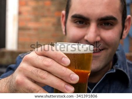 Man raising a glass of beer in a pub.