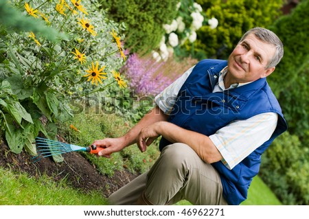 Man raking garden - stock photo