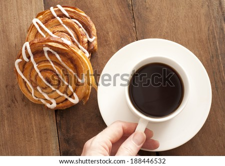 Man reaching for a cup and saucer of full roast espresso coffee with fresh Danish pastries for a refreshing coffee break, high angle view on wood - stock photo