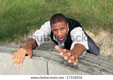 Man reaching for help while climbing a wall - stock photo