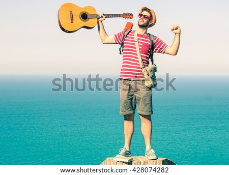 Man reaching the top exulting with arms raised up on blue ocean background - Cheering traveler guy standing at summit of hill - Casual style concept of climb to success and achievement of life goals - stock photo