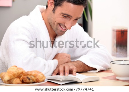man reading a book at breakfast