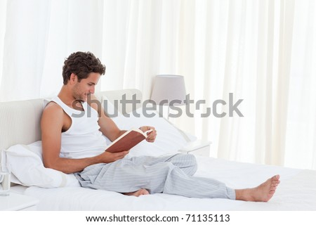 Man reading a book on his bed at home - stock photo