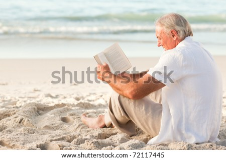 Man reading a book on the beach - stock photo