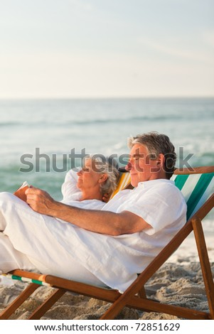 Man reading a book while his wife is sleeping - stock photo