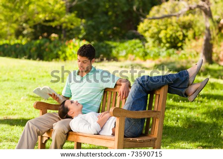 Man reading a book with his girlfriend - stock photo