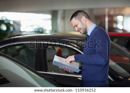 Man reading a file in a dealership - stock photo