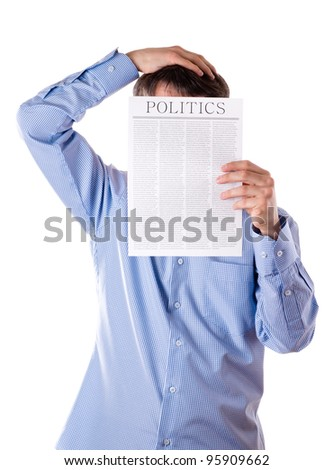 Man reading a newspaper with inscription POLITICS - stock photo