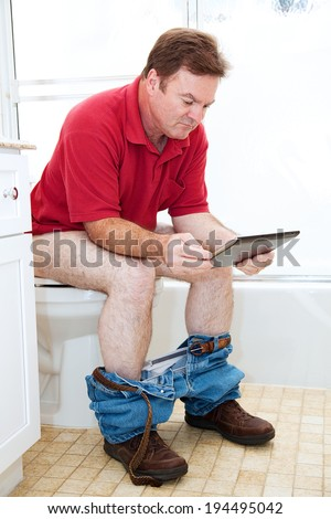 Man reading a tablet pc while using the toilet in the bathroom.