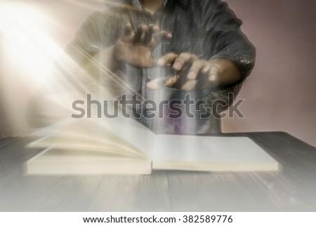 Man Reading Bible And Praying (Blur) - stock photo