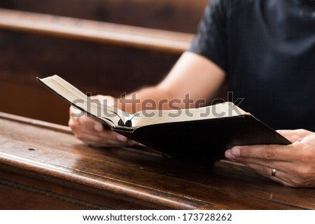 Man reading Bible in a church - stock photo