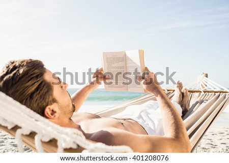 Man reading book in hammock on the beach - stock photo
