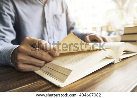 Man reading book in library or cafe. Retro filter effect,soft focus,low light.(selective focus) - stock photo