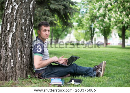 Man reading book in park, sitting under a tree. Relaxing outdoors reading. - stock photo