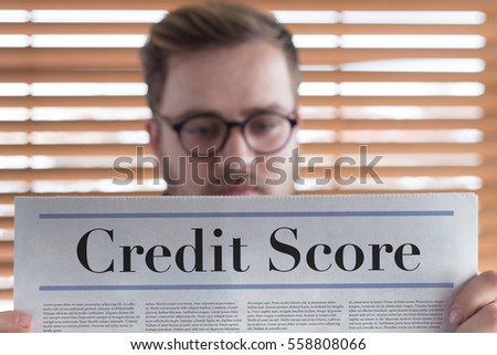 Man reading Credit Score headlined newspaper