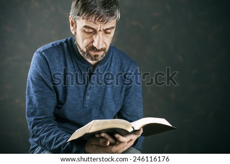 Man reading from the holy bible, close up - stock photo