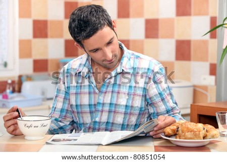 Man reading his newspaper at the breakfast table - stock photo