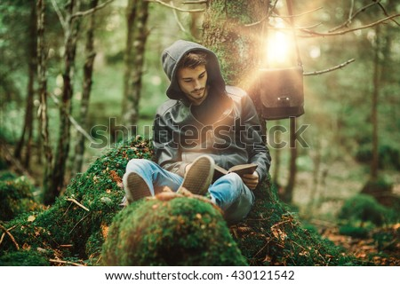 Man reading in nature and relaxing outdoors, freedom and individuality concept - stock photo