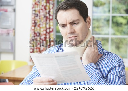 Man Reading Letter After Receiving Neck Injury - stock photo