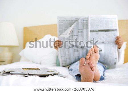man reading newspaper in bed - stock photo
