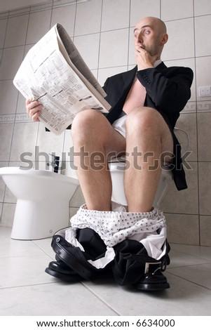 Man reading newspaper on toilet, expressing surprise - stock photo