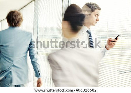 Man reading sms while walking in office corridor - stock photo