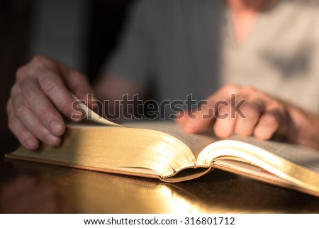Man reading the Bible in dim light