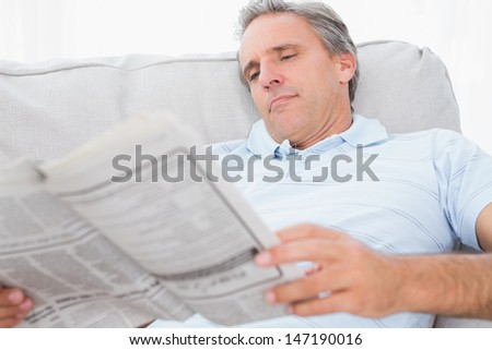 Man reading the news on couch at home in living room