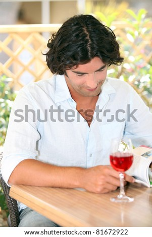 Man reading with a glass of rose in the sunshine - stock photo