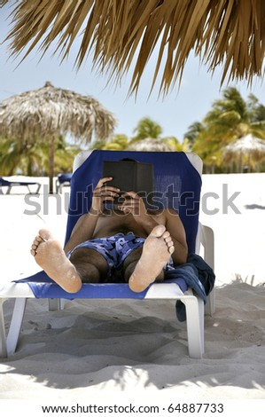 Man reads a book on the beach - stock photo
