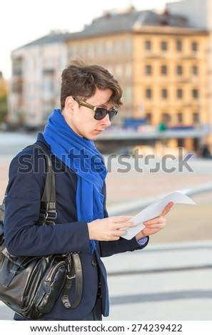 Man reads the ad, he is looking for a job. Read the ad on employment. Applicant for the vacancy. Search for a job. Business man on background of the city. Looking for a job. Documents in the hands. - stock photo