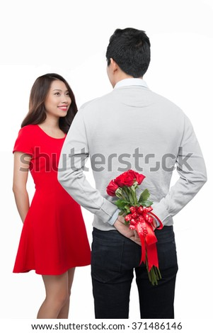 Man ready to give flowers to girlfriend. Man preparing to surprise his friend by giving her a bunch of flowers with focus on the man and the flowers - stock photo